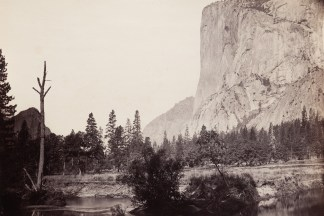 19th century photograph of a river in the foreground with a sheer rock cliff face in the distance