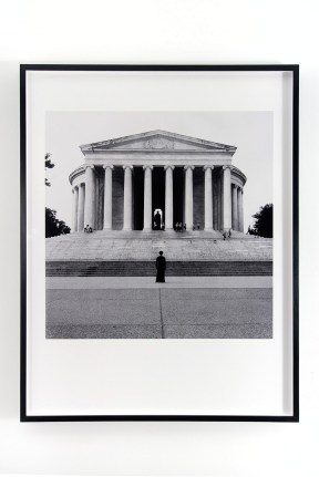 Black and white photograph of a person standing at the foot of the steps to a rotunda with a sculpture inside