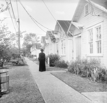 Black and white photograph of a woman in a black dress standing on a sidewalk in front of identical white single story houses