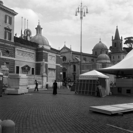 Black and white photograph of a person standing in a plaza scattered with a few tents and construction materials
