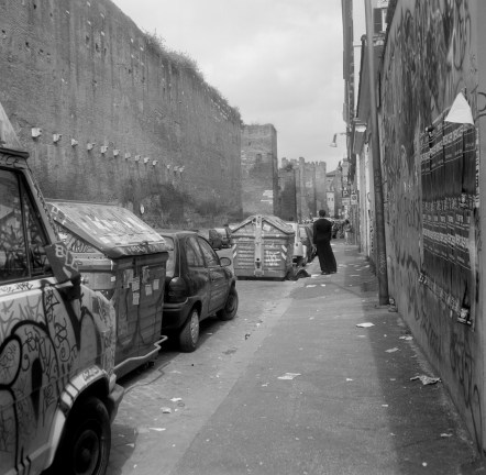 Black and white photograph of a person standing next to graffitied dumpsters and vehicles parked on a back street