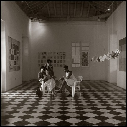 Black and white photograph of three people seated on plastic lawn chairs in an art gallery