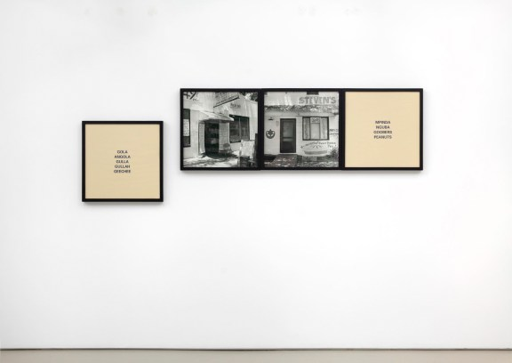 Two black and white framed photographs of storefronts framed on either side by two panels of black text on a plain tan background
