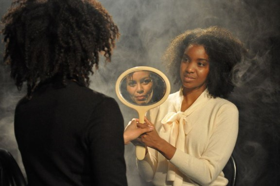 Color photograph of a young woman presenting a hand mirror to another woman looking at her reflection