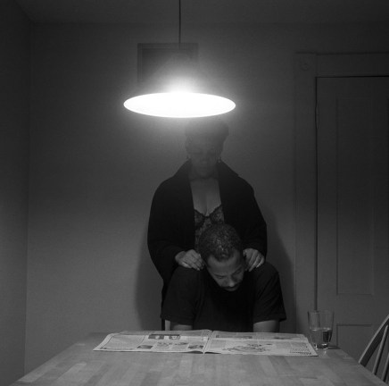 Black and white photograph of a kitchen table lit by an overhead lamp; at the end of the table, an African American man leans over a newspaper, an African American woman stands behind, with hands on his shoulders.