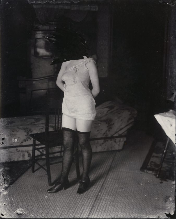 Black and white photograph of a woman in lingerie standing in front of a chair, with her face scratched out