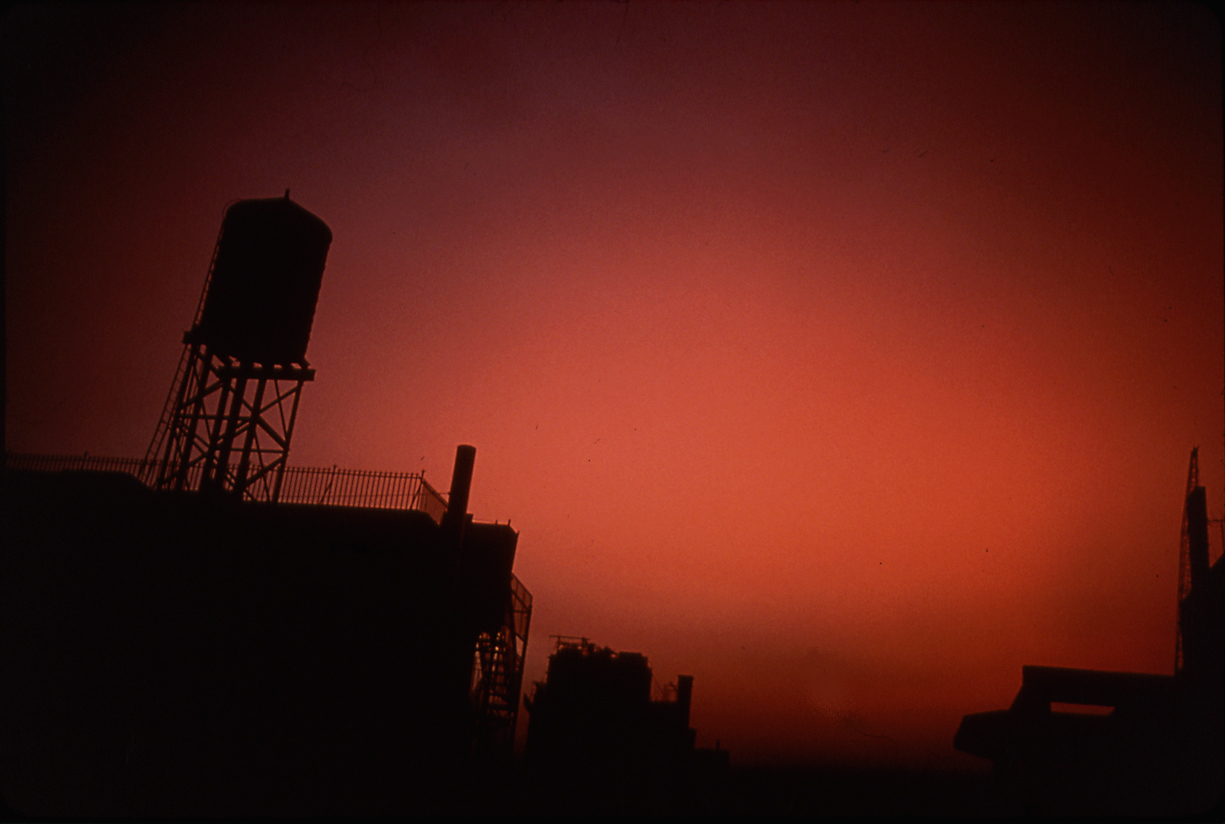 Color photograph of silhouetted industrial buildings against a red sky