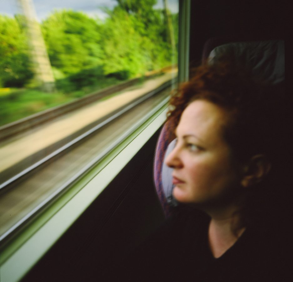 Color portrait of woman looking out through the window of a moving train, blurred tracks visible outside