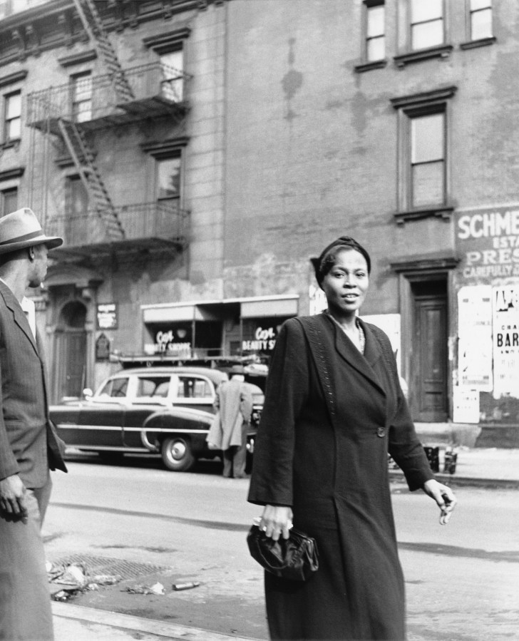 black-and-white photograph of a woman walking down the street holding a purse