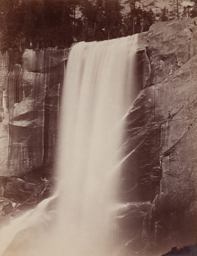 19th century photograph of a large waterfall, coming off a cliff