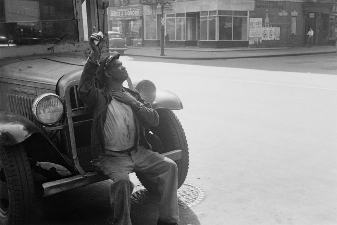 Black-and-white photograph of an African American man seated on the front bumper of a parked car.