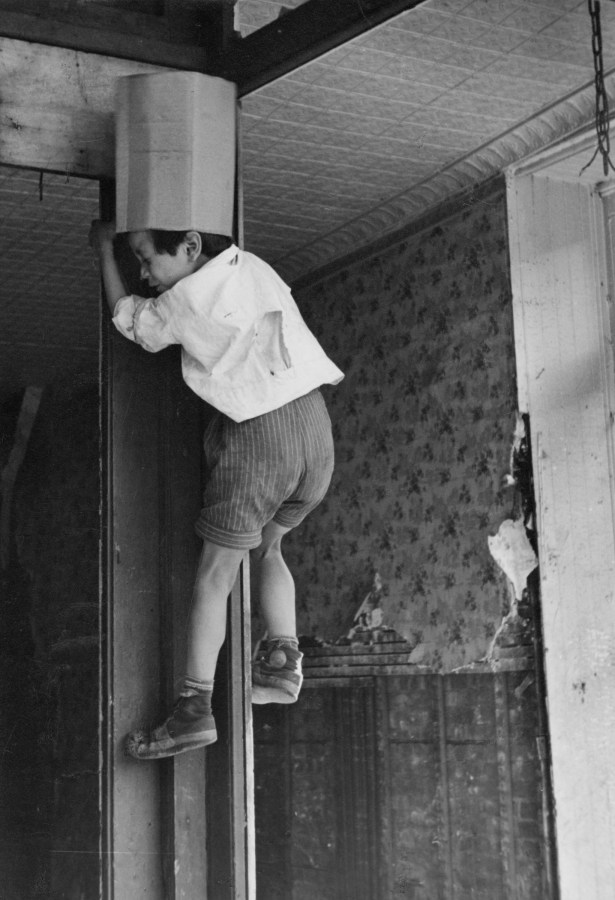 Black-and-white photograph of a young boy climbing a wall in a disheveled hallway.