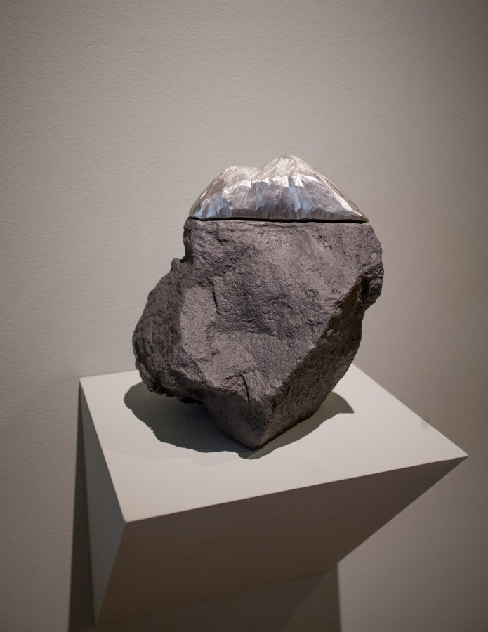 Stone seated on a shelf capped with a silver slice on top