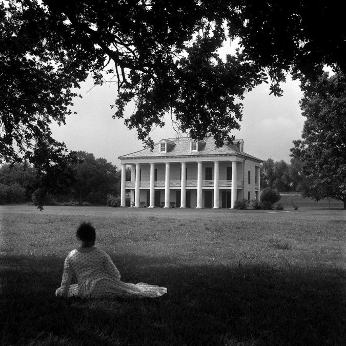 Black and white photograph of a woman seated beneath a tree looking at a manor house in the distance