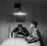 Black-and-white photograph of an African American couple seated at a dinner table, eating lobster.