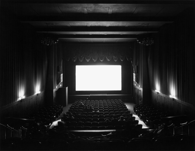 A black and white photograph of a movie theater with a bright white screen, and audience watching the film