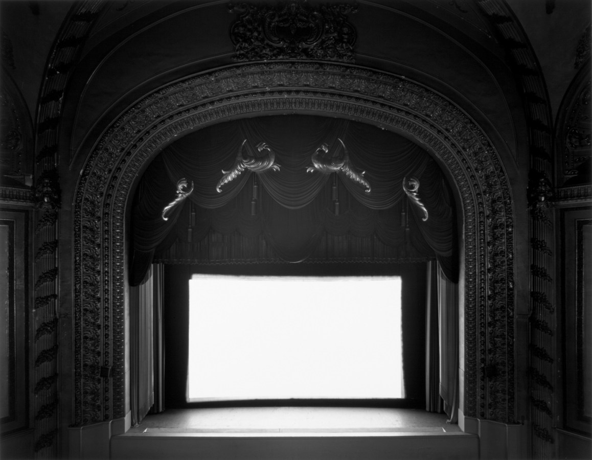 A black and white photograph of an ornately decorated classic movie theater with a bright white screen