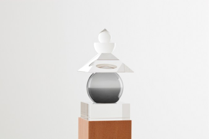 Glass sculpture of stacked geometric shapes with a black-and-white photo of a seascape inserted in the central orb