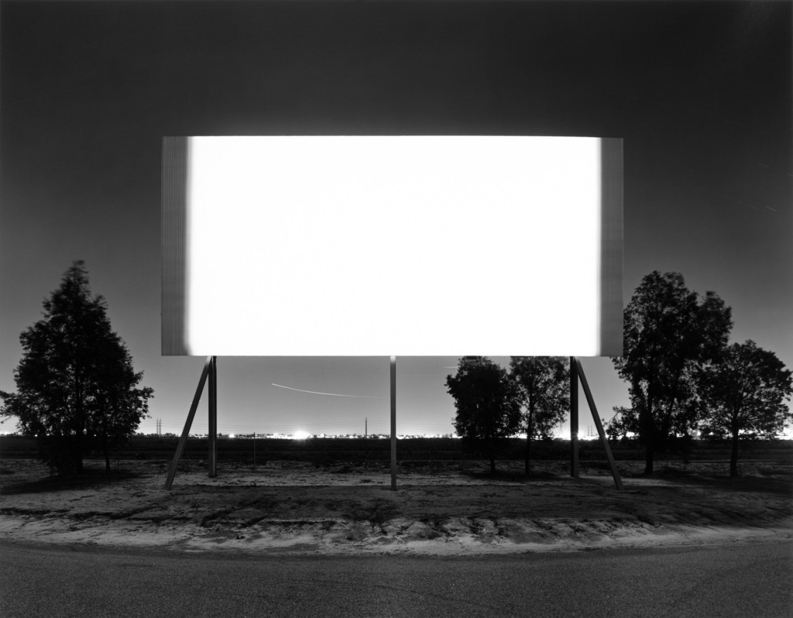 A black and white photograph of a bright white screen at a drive-in, with trees behind it and a city in the distance