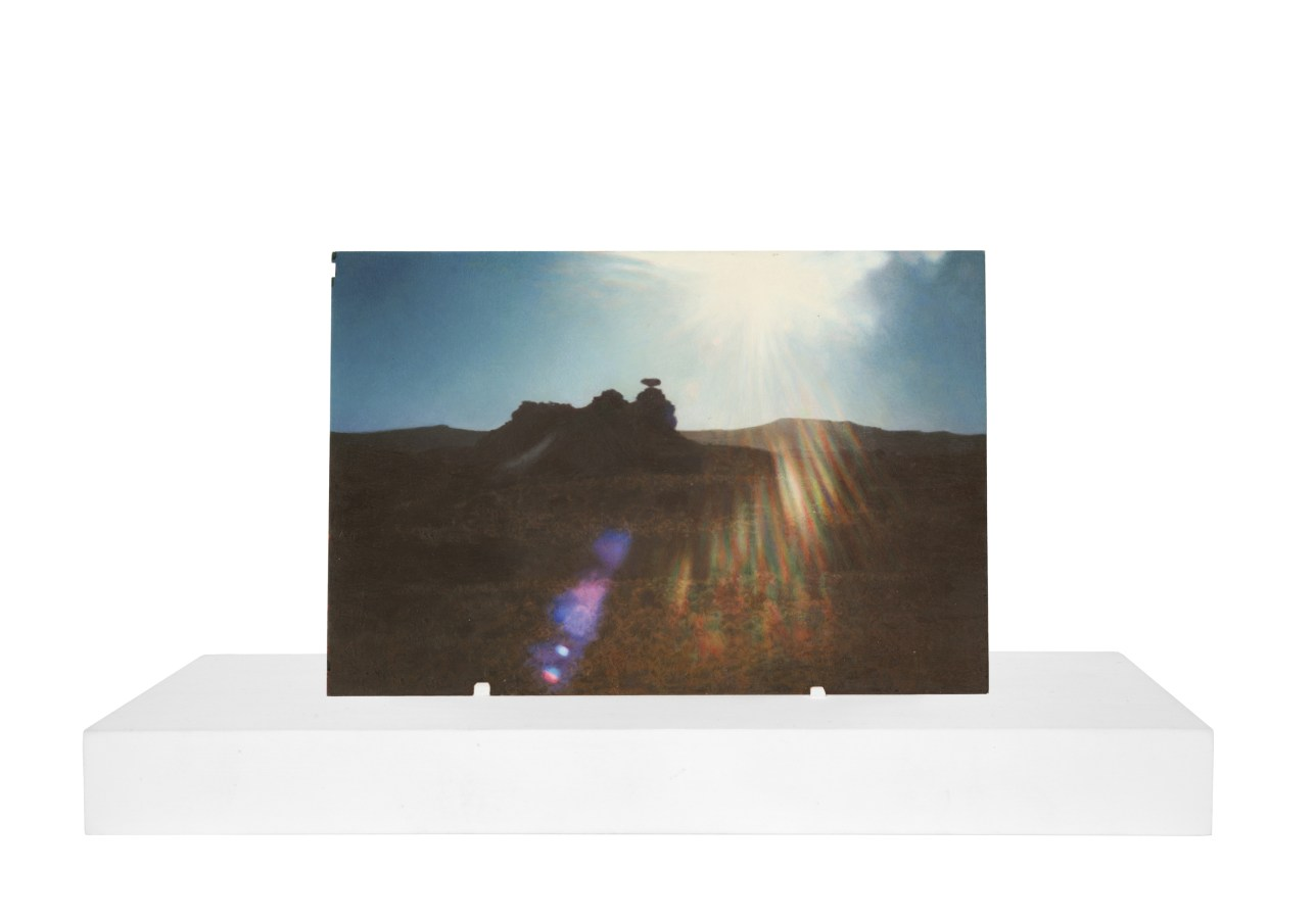 A painting of a vernacular photograph, on a white stand, of a rock formation out in the desert. The sun has caused a rainbow light flare in the center of the image.