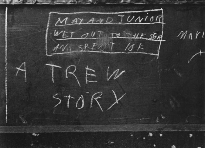 Black-and-white photograph of chalk writing on sidewalk.