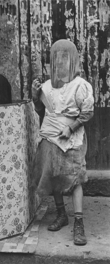 Black-and-white photograph of a child in a makeshift costume and mask holding a large chef's knife.