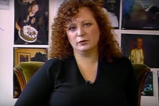 Video still of a woman in front of a wall of photographs