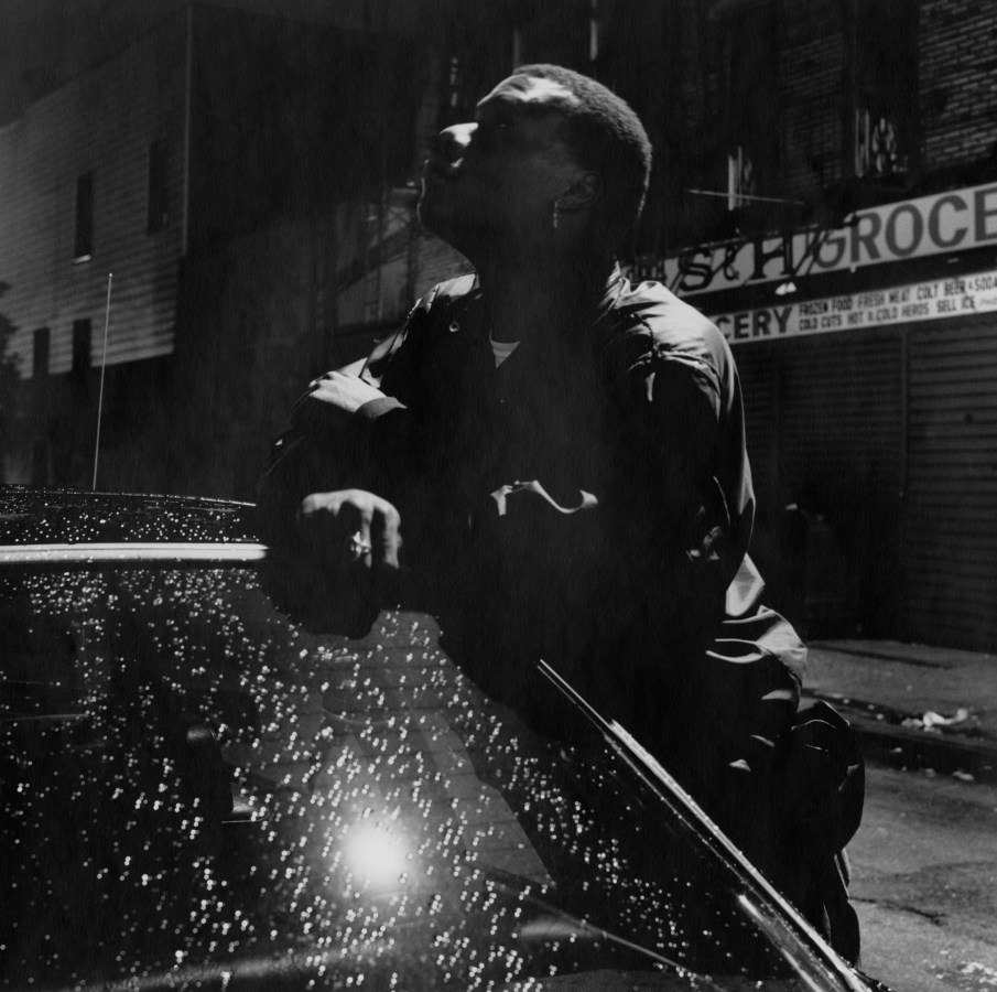 Black-and-white nighttime photograph of a man leaning on a car roof.