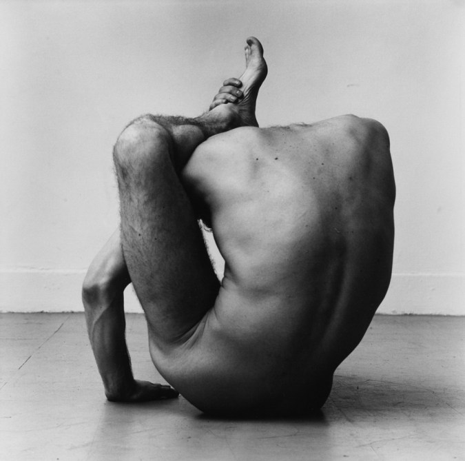 Black-and-white photograph of a nude man with his ankle hooked over his neck, seen from the back.