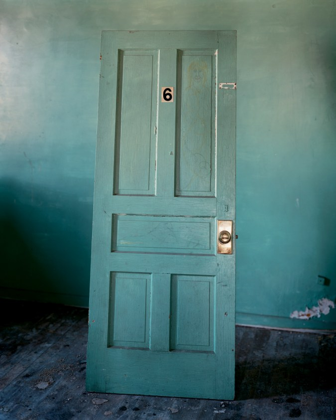 Color photograph of a turquoise door leaning against a turquoise wall