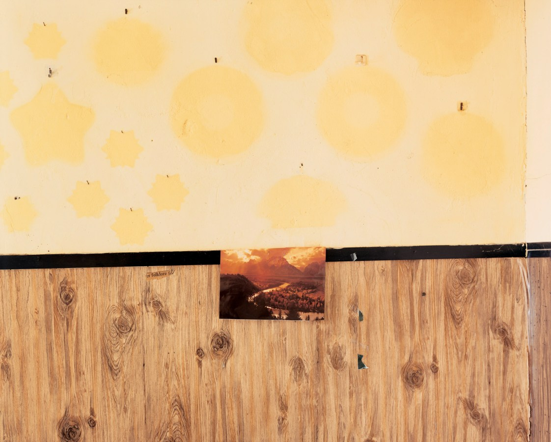 Color photograph of a post-card sized picture of a mountain river tacked to a wall of wood paneling and yellow patterned wallpaper