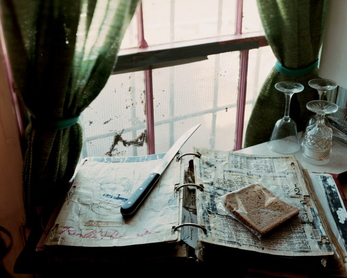 A color photograph of a book in front of a window with green curtains. On top of the book is a long knife and a piece of brown bread in a plastic bag.