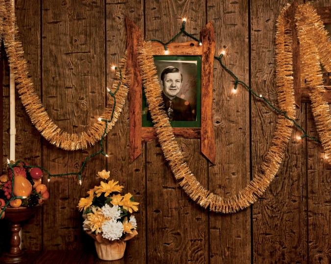 A color photograph of a wood-paneled room, with a black and white autographed portrait hung on the wall. Gold streamers are hung across it.