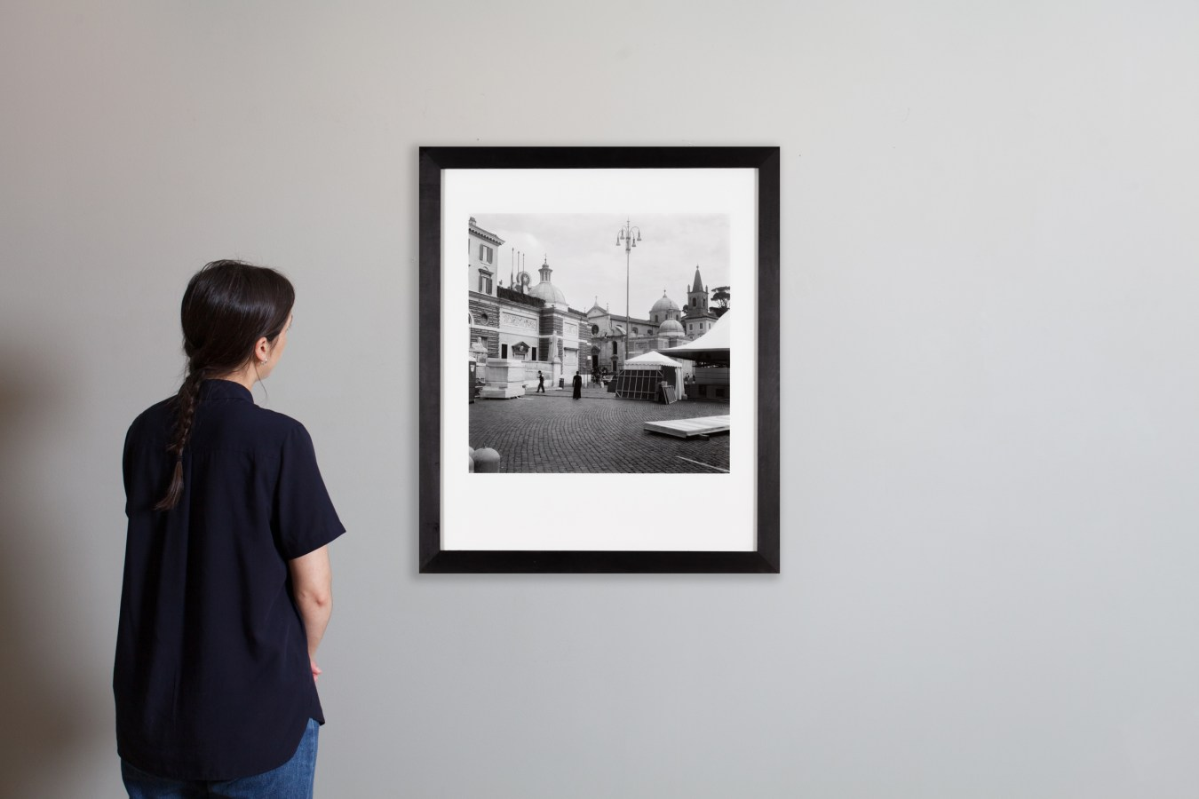 Installation photograph of a person observing a framed black and white photograph of a woman in a Roman plaza