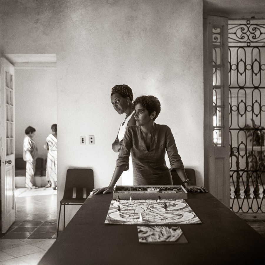 Sepia toned photograph of a woman leaning on a table in front of a boardgame and another woman staring directly into the camera behind her.