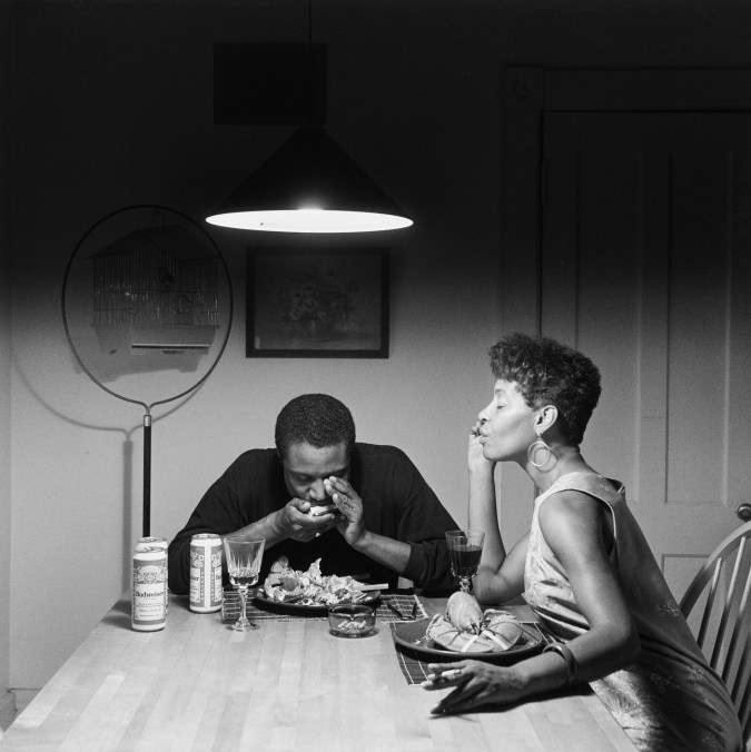 Black and white photograph of an African American couple seated at a kitchen table set with lobster dinner, the man playing a harmonica and the woman listening with eyes closed.