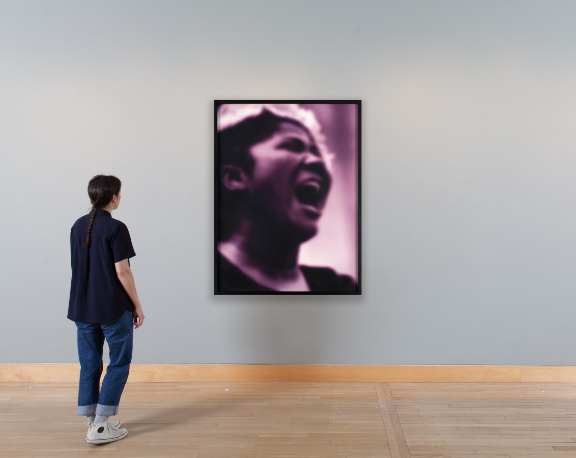 Installation photograph of a purple-toned portrait of a woman singing