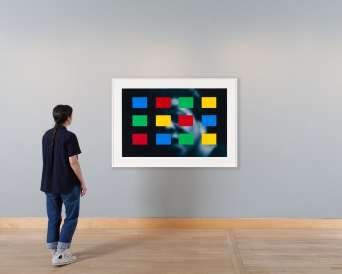 Person standing in front of a framed artwork showing a soft-focus blue-toned portrait overlayed with blue, yellow, green, and red color blocks.