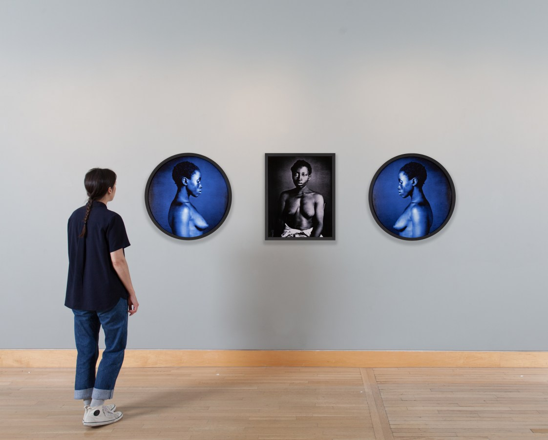 Installation view of a woman looking at a triptych of framed photographs.