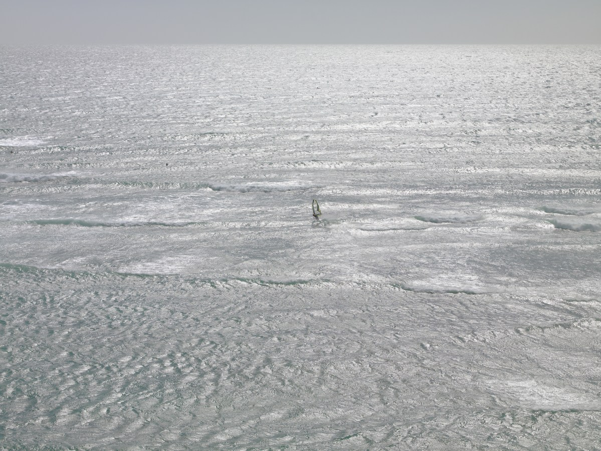 Color photograph of a lone windsurfer on a choppy silver sea