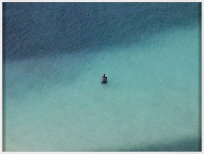 Framed color photograph of a lone figure standing in a shallow blue sea