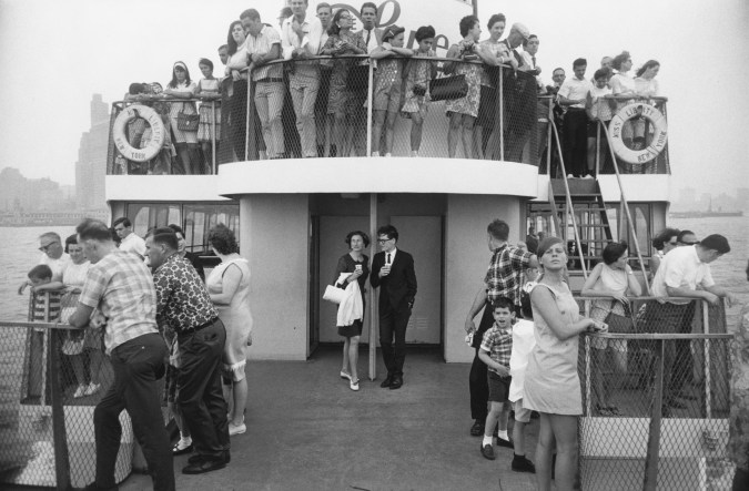 Black-and-white photograph of a young man and woman at the front of a two-story ferry filled with people looking out over the railings