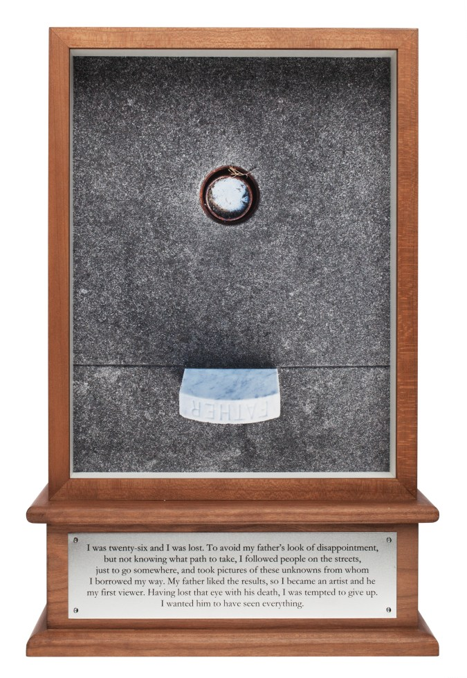 """A color photograph of a ring buried in the ground, above a gravestone marker reading """"Father."""" The photograph is encased in a wooden box with a silver plauqe."""