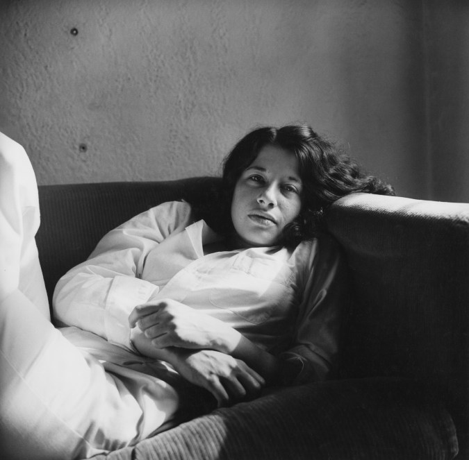 Black-and-white photograph of Fran Lebowitz reclining on a couch.