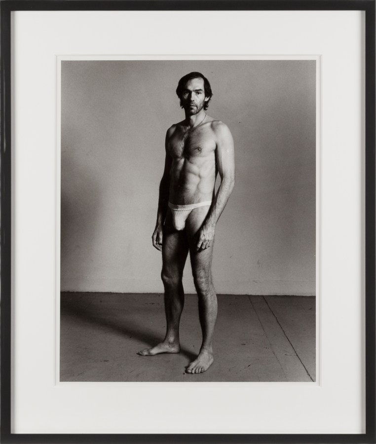 Framed black-and-white vertical photograph of a standing man wearing a jock strap.