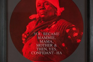 """A circular photograph printed in red and black tones depict a woman framed in a black frame. Text printed across the woman reads """"You Became Mammie, Mama, Mother, Then, Yes, Confidant-Ha."""""""