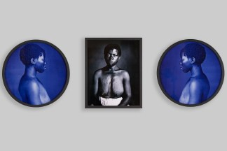 Installation view of one framed black and white portrait of an enslaved woman with her blouse removed, staring directly into the camera, accompanied by two framed blue and black portraits of the same woman looking down in profile.