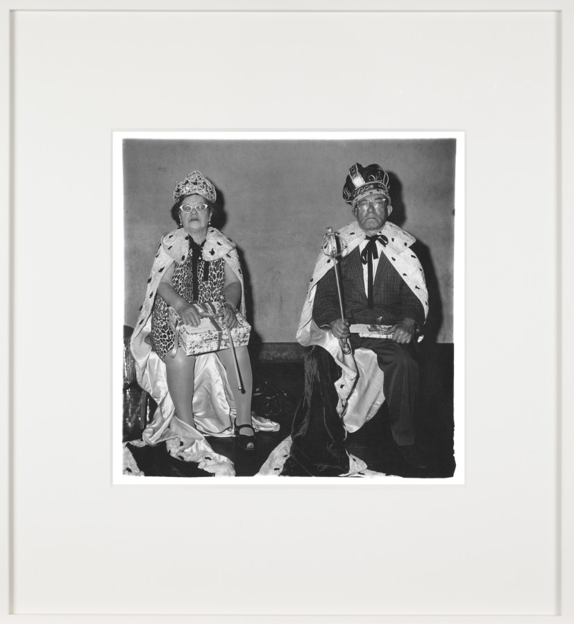 Framed black-and-white photograph of an elderly couple wearing king and queen costumes.