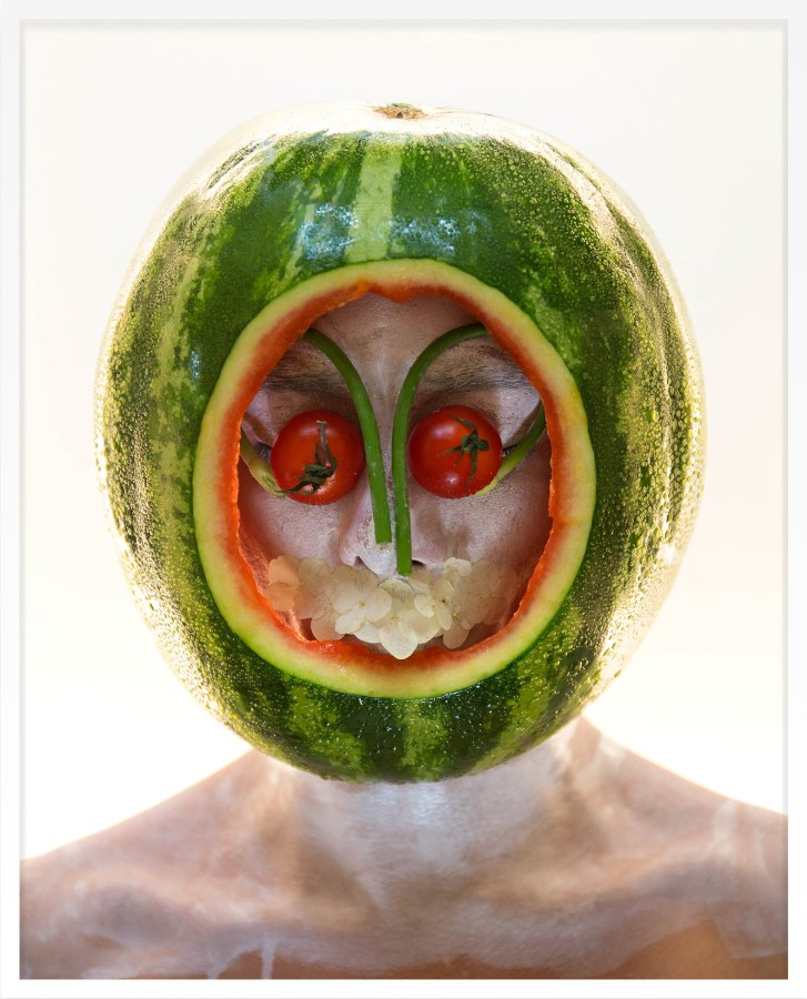 Framed color photograph of a person with a watermelon over their head.