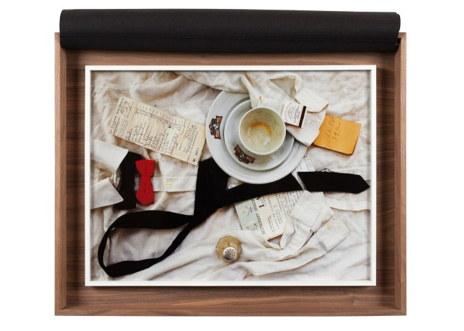 A wooden box which holds a framed color photograph of a still life. The still life is of a waiter's shirt, with an empty coffee cup on top and restaurant checks scattered throughout.